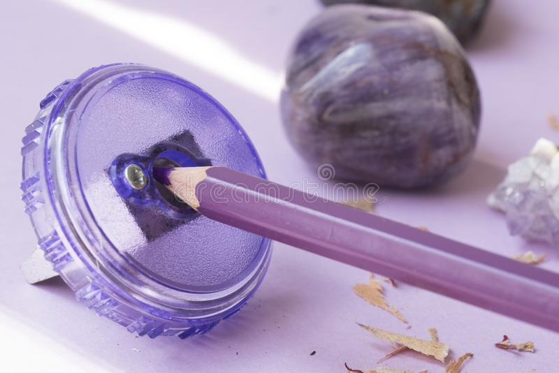 Close up of purple pen, with sharpener, stones and shavings stock image
