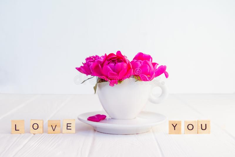 Close up purple pink peony flowers bouquet in a decorative cup and saucer and message I love you spelled in wooden blocks on white. Wooden background stock photo