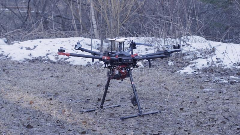 Close-up of quadcopter takes off. Clip. Powerful model of new generation quadcopter is on ground preparing for takeoff. Quadcopter is on forest background with royalty free stock photography