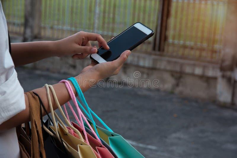 Close up que o telefone celular guardava pela mão da senhora, está pressionando no telefone celular para comprar em linha e leva  imagens de stock royalty free