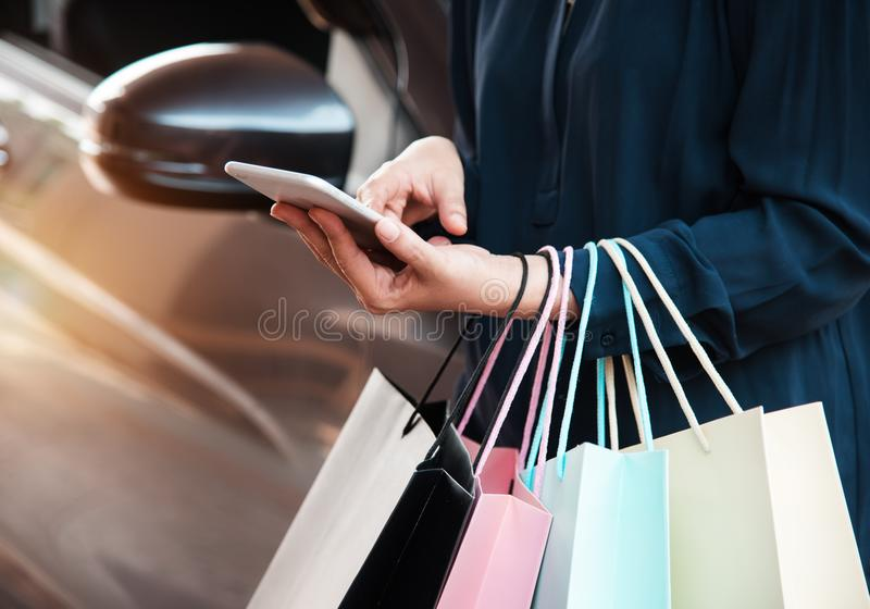 Close up que a senhora está pressionando no telefone celular para comprar em linha e está guardando sacos de compras coloridos no fotos de stock