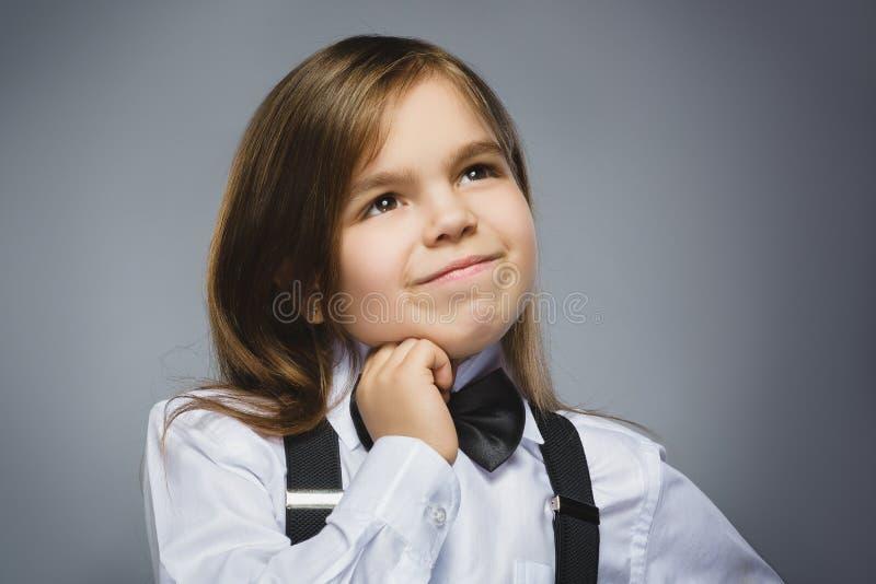 Close up que sonha a moça que olha acima contra Gray Background fotografia de stock