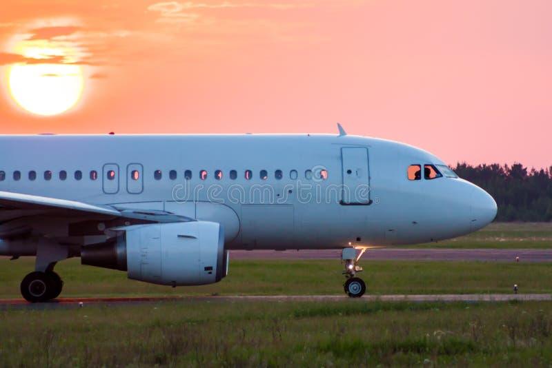 Close-up que taxiing um avião branco do passageiro contra o sol de ajuste foto de stock