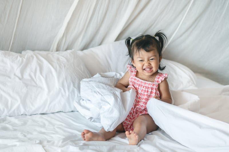 Close up que uma menina se senta na cama com a cara do sorriso na manh? fotos de stock