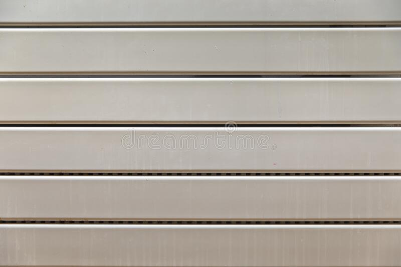 Close-up on a radiator composed of horizontal heating panels. They are white and worn and have interstices made up of small holes stock photos