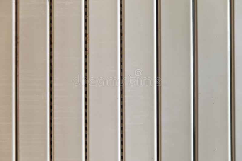 Close-up on a radiator composed of vertical heating panels. They are white and worn and have interstices made up of small holes royalty free stock photo