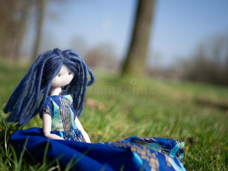 Close up of a rag doll with blue hair sitting outside in a field stock images