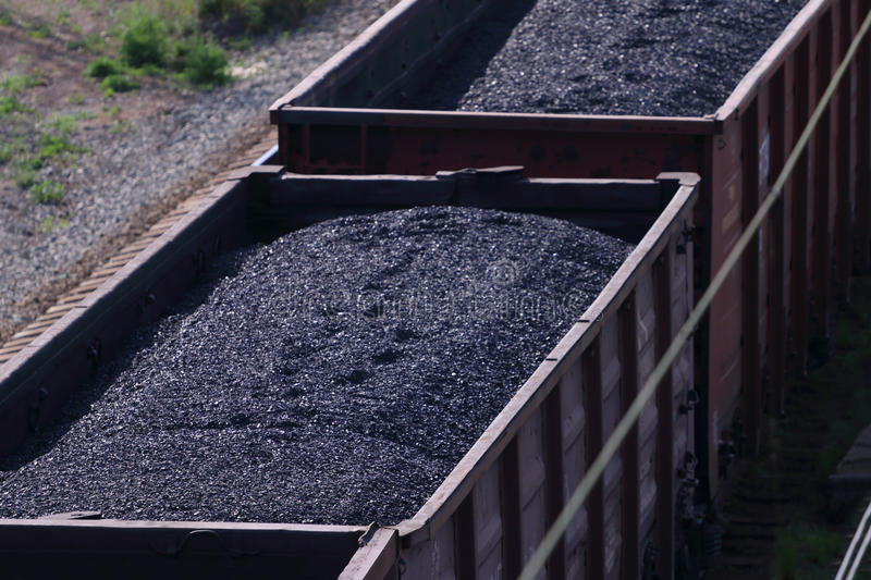 Close-up railroad tracks with wagons with coal. On summer day royalty free stock image