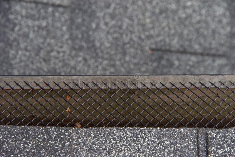 Close up on rain gutter covered with mesh leaf guard. Close up on section of rain gutter residential home, free of leaves and debris, covered with mesh, which royalty free stock photos