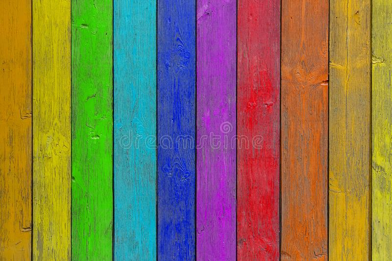 Close-up of a   wooden  wall. Close-up of a   rainbow wooden  wall  or fence painted a very long time and the paint peeled off.  Fun background for kids decor stock image