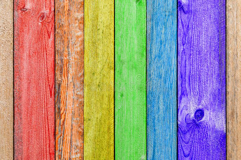 Close-up of a   rainbow wooden  wall. Or fence painted a very long time and the paint peeled off.  Fun background for kids decor and design stock photography