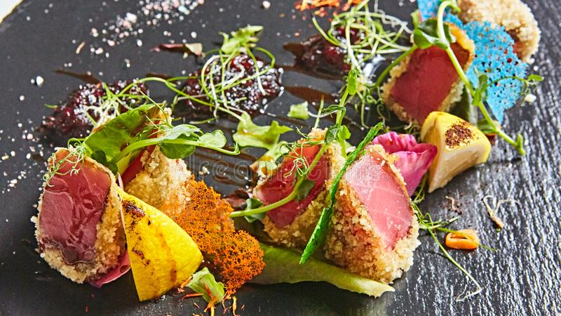 Close up of rare seared Ahi tuna slices with fresh vegetable salad on a plate. royalty free stock photo