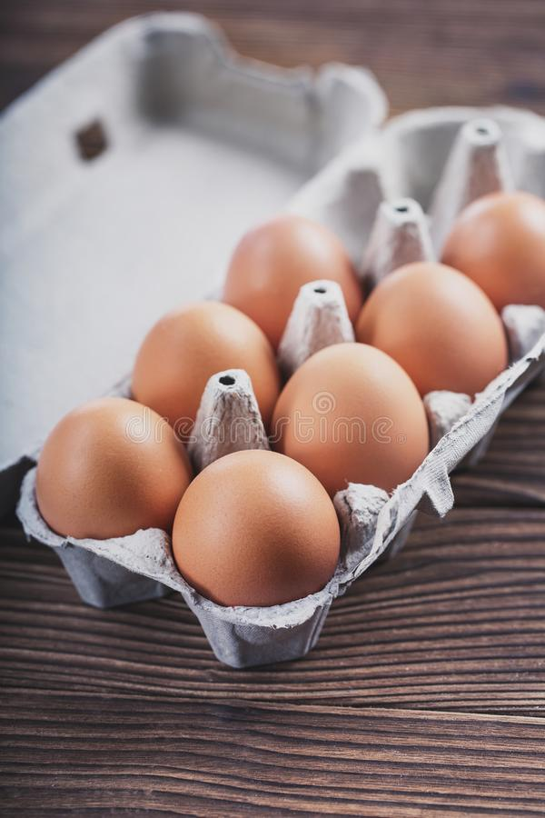 Close-up of raw chicken eggs in a box. Eggs on an old wooden table royalty free stock photography