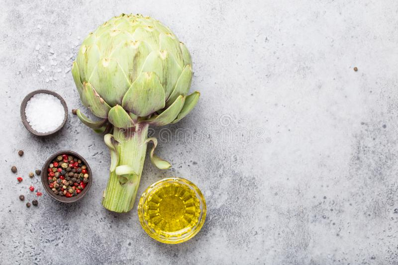 Raw fresh artichoke. Close-up of raw fresh artichoke with seasonings ready to cook, great as vegetarian food or ingredient for healthy salads and diets, grey stock image