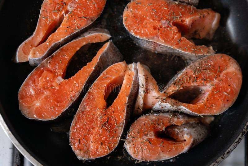 Close-up of raw pink salmon steaks in a frying pan, top view. Fresh seafood for frying. stock photo