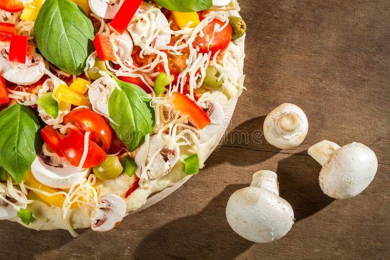 Close-up of raw pizza and three mushrooms royalty free stock images