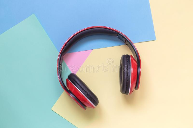 Close up of read headphones on multicolored background. Music minimal concept. Red headphones isolated on colorful pastel background flat lay royalty free stock photography