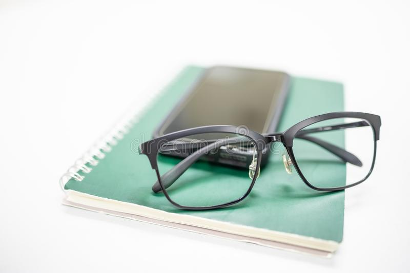 Close up of reading glasses on mobile smartphone and green notebook on white table. Education technology and work concept royalty free stock images