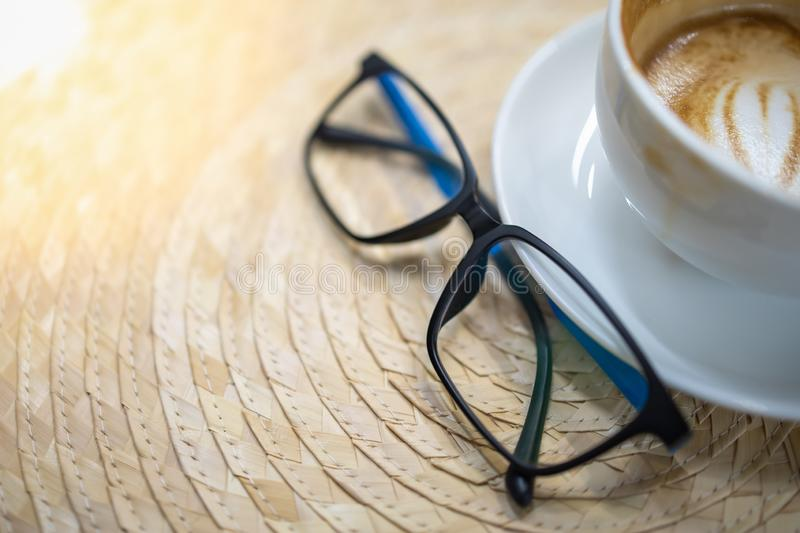 Close up of reading glasses and white cup of hot coffee latte with heart shape art on wickerwork.  royalty free stock photography