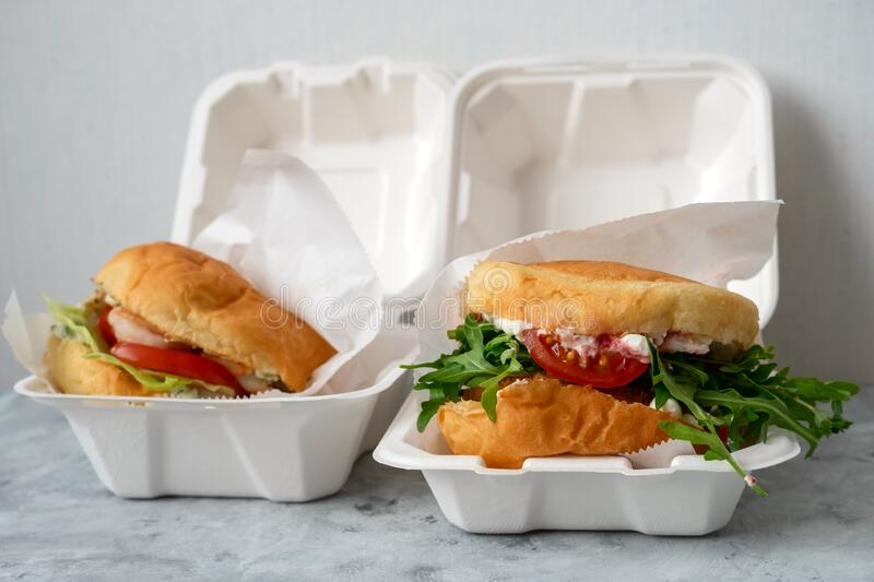 Real burger with arugula salad in a plastic container on the table, food delivery concept. Close up of real burger with arugula salad  in a plastic container on stock photography