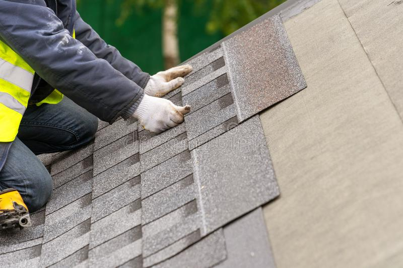 Workman install tile on roof of new house under construction royalty free stock images