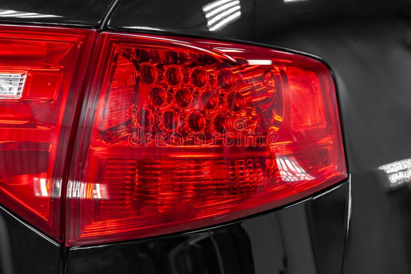 Close-up on the rear LED brake light of red color on a black car in the back of a suv after cleaning, polishing. Close-up on the rear LED brake light of red stock photos