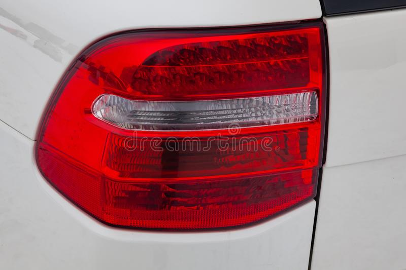 Close-up on the rear LED brake light of red color on a white car in the back of a suv after cleaning, polishing and detailing in. The vehicle repair workshop royalty free stock photo