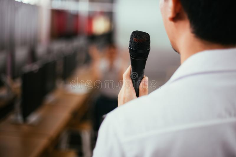 Close up of rear male businessman speaking and making a lecture in public speaking event in small room. Close up of rear male businessman speaking and making a stock photos