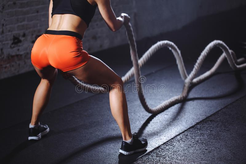 Rear view of tonned woman training with battle rope in cross fit gym. Close up rear view of tonned woman training with battle rope in cross fit gym stock images
