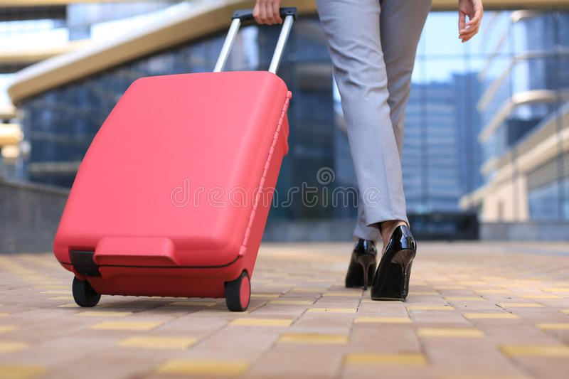 Close up rear view of young woman pulling luggage while walking outdoors stock photos