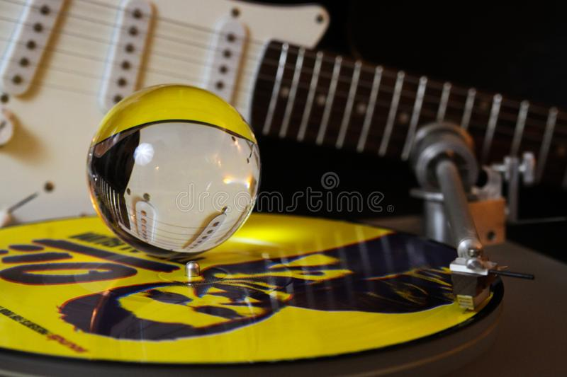 Close up of record player with yellow punk vinyl LP and crystal sphere glass ball und blurred electric guitar with black royalty free stock images
