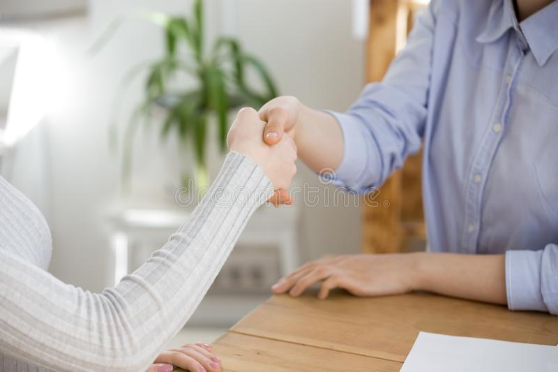 Close up of recruiter handshake female job candidate in office. Close up of HR manager handshake female job applicant greeting at interview, businesswomen or royalty free stock image