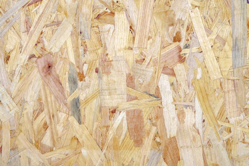 Close up of a recycled compressed light brown wood chippings board textured background. Abstract texture background royalty free stock image