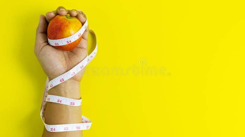 Close up of the red apple on the left hand Wrapped around a tape measure royalty free stock images