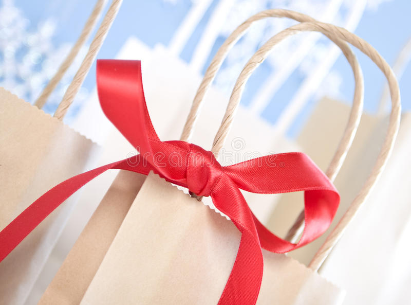 Close up of red bow tied to brown paper bag. Close up of red ribbon bow on brown craft paper bag stock photography