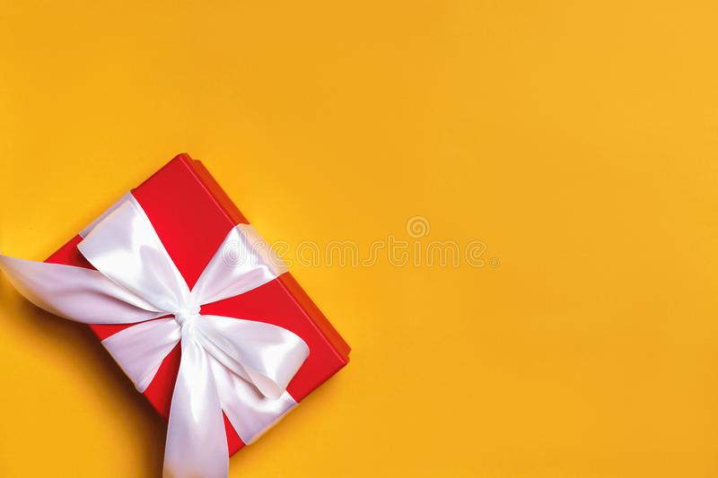 Close up of a red box with a gift and a white ribbon on a yellow background royalty free stock images