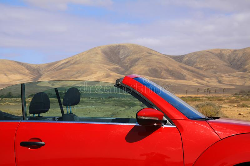Close up of red cabriolet in dry desert landscape with mountains background - Lanzarote, El Cotillo royalty free stock photo