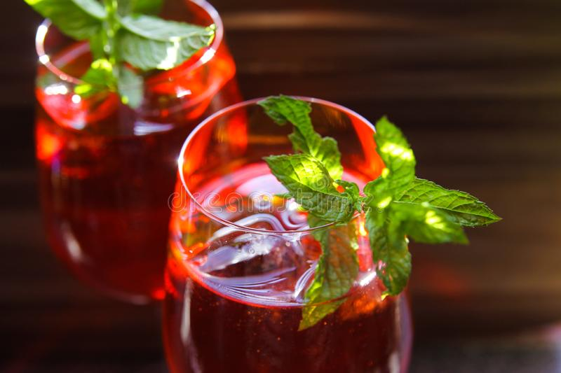 Close up of red cocktail with ice cubes green mint leaves in wine glass stock photography