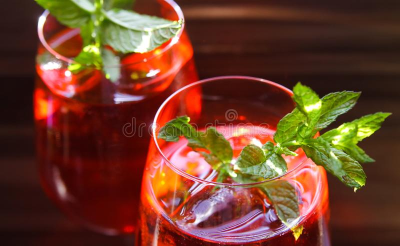 Close up of red cocktail with ice cubes green mint leaves in wine glass royalty free stock image