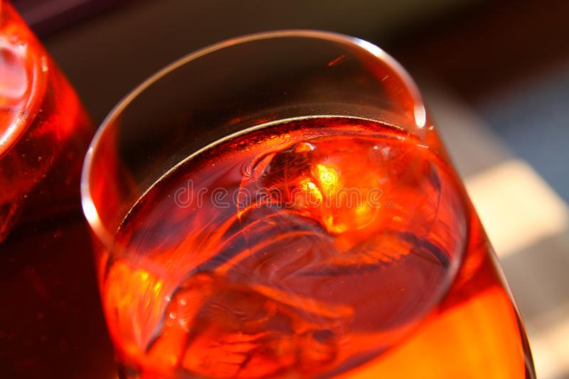 Close up of red cocktail with ice cubes in wine glass royalty free stock photos
