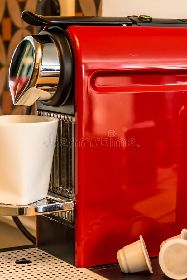 Close-up of a red cup-based coffee machine, pouring coffee. In a white mug stock images