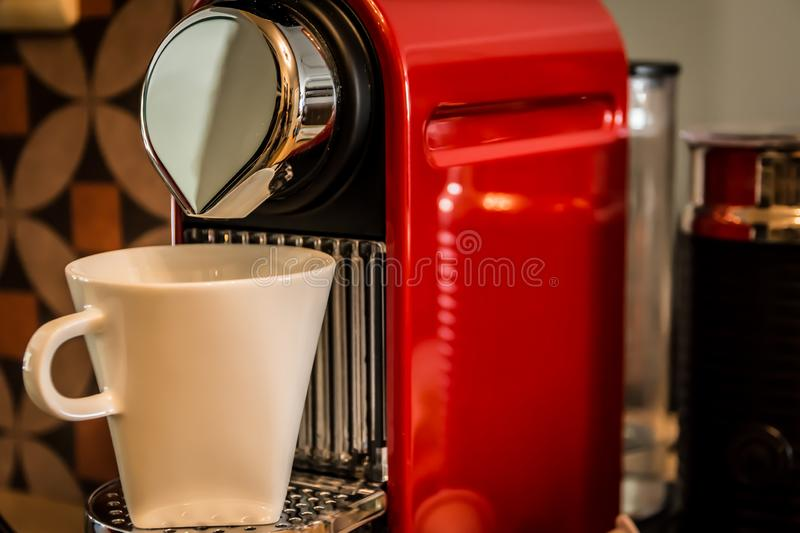 Close-up of a red cup-based coffee machine, pouring coffee. In a white mug stock photo
