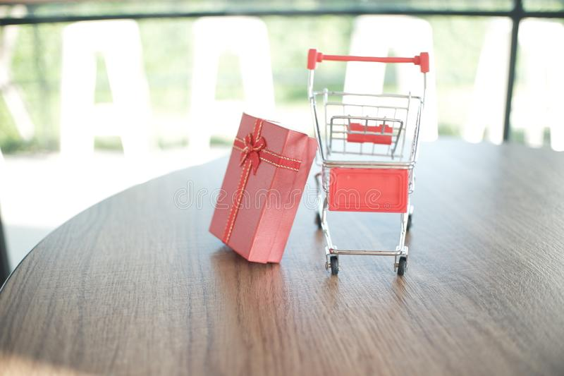 Close up red gift box and shopping cart on table for shopping and e-commerce concept.  stock photography