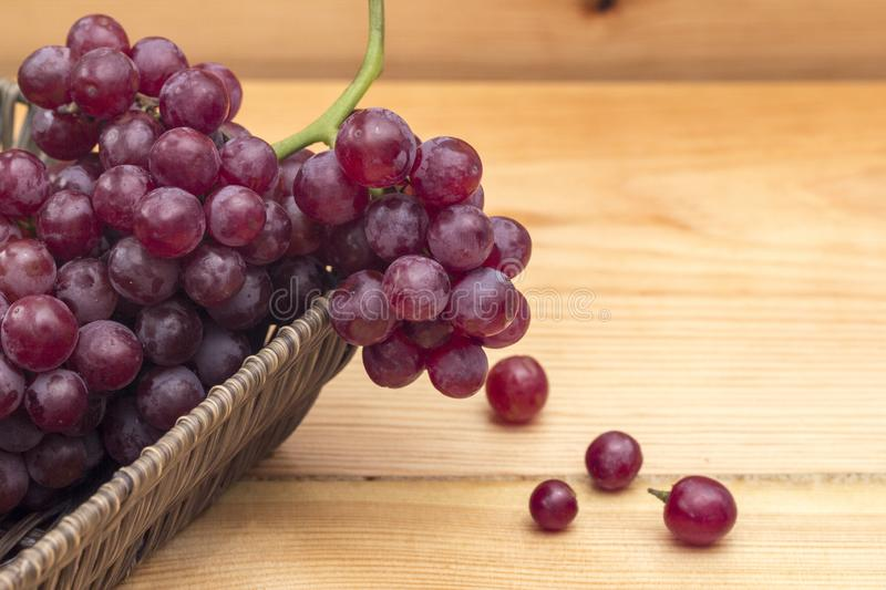 Close up of red grapes in a basket on a wooden background. royalty free stock image