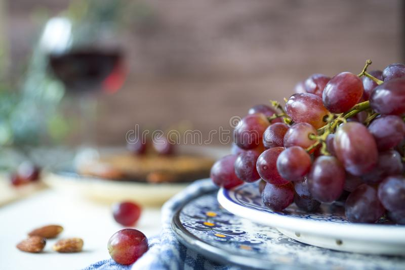 Bunch red grapes in blue  bowl, against brown blur background. stock images
