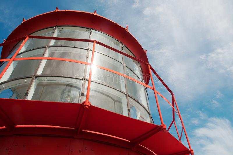 Close-up of a red lighthouse light with a blue sky in the background royalty free stock photo