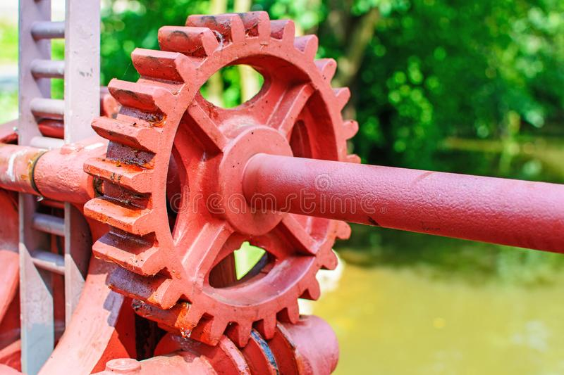 Close-up of a red metal gear on the floodgate. Mechanism to open the dam. Old toothed wheel on the river. Transfer to the opening of the dam. Old cogwheel stock images