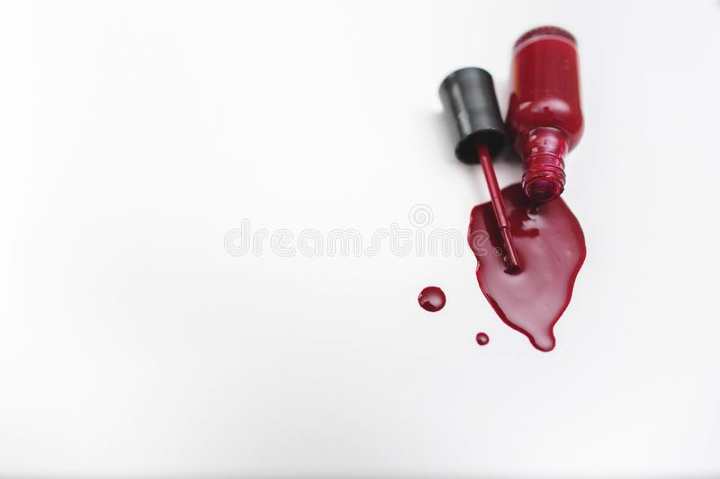 Close up of a red nail polish bottle and drop on white background royalty free stock photo