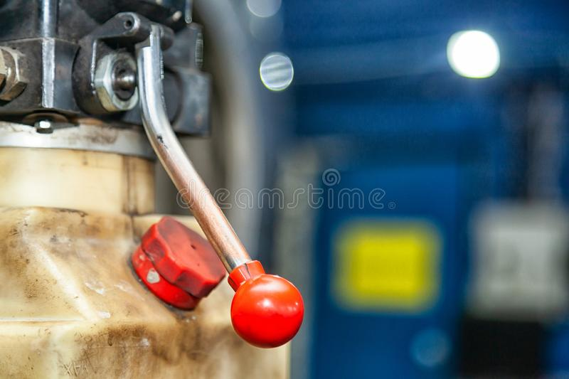 Close-up red new car lift lever. In a car repair shop. Apparatus for Pressure Relief stock photos