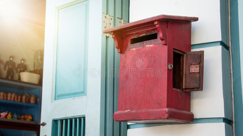 Close up of red old vintage wooden mailbox in front of vintage store. royalty free stock images